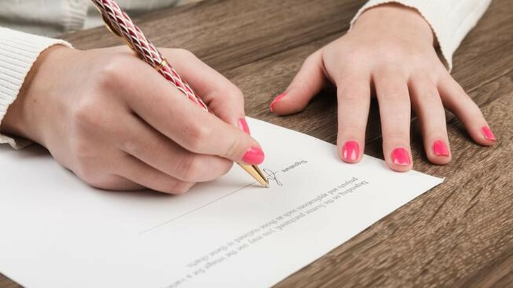 person preparing to sign a contract