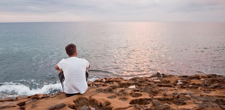 Man sitting alone by ocean