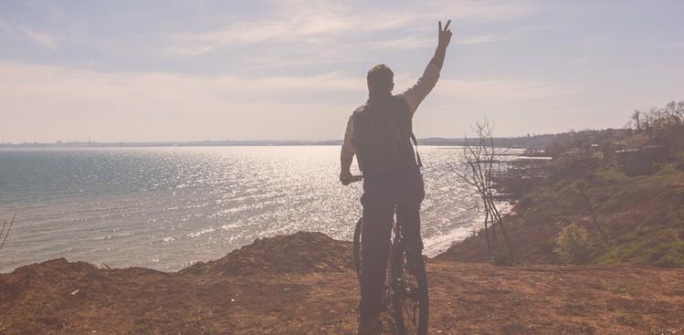 man riding bike into sunset