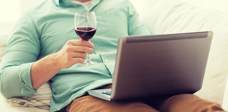 Man drinking on computer
