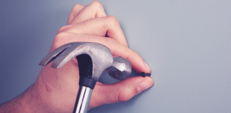 Hammering a nail into the wall