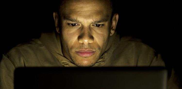 man typing on laptop at night
