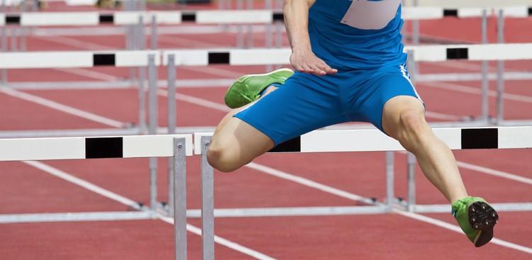 Hurdle runner jumping over hurdles