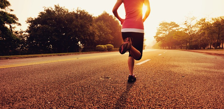 Person running on road towards sunrise
