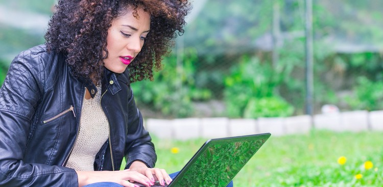 Woman with curly hair using laptop in park