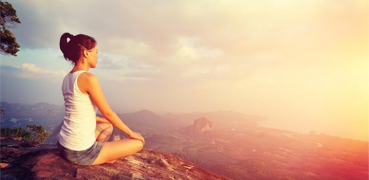 Woman doing yoga on top of mountain