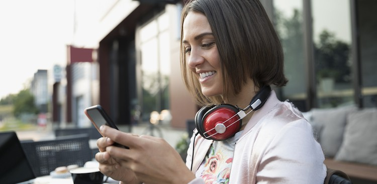 woman with headphones on her phone smiling outside