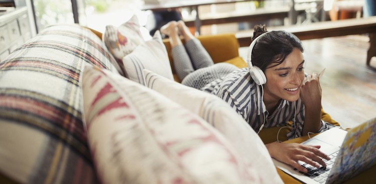 woman with headphone on smiling at laptop on couch working