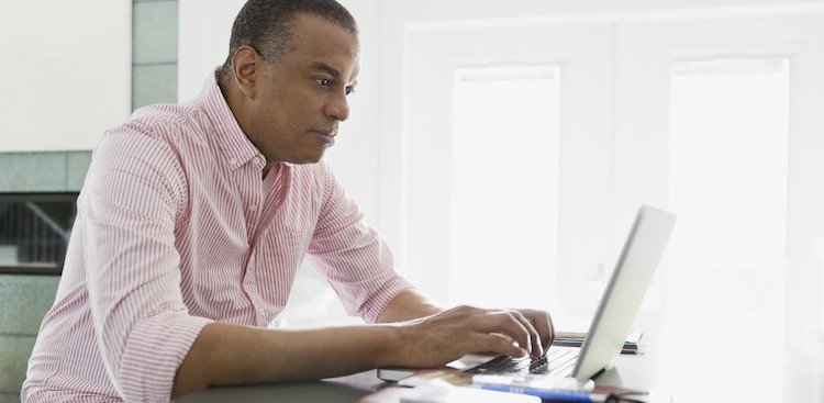 man serious at a desk on a laptop