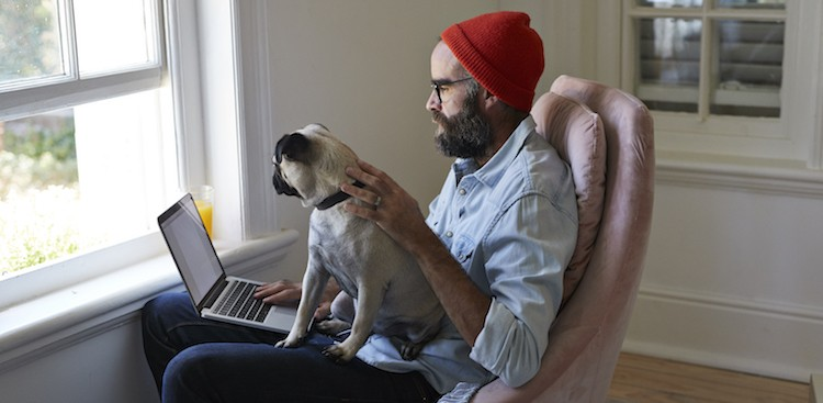 man with hat facing window with dog and laptop