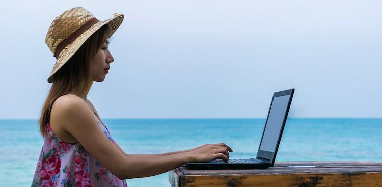 woman outside wearing a hat on a laptop