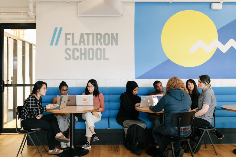 students with laptops sitting at tables in a Flatiron School cafe