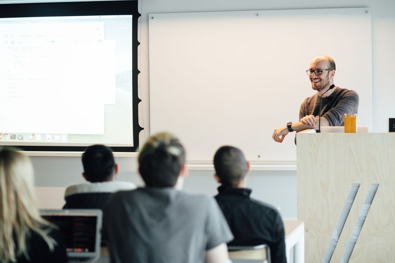 instructor standing at a podium at the front of a classroom