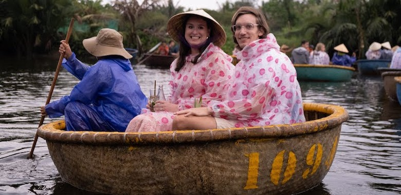 two people in pink rain ponchos being rowed in a boat