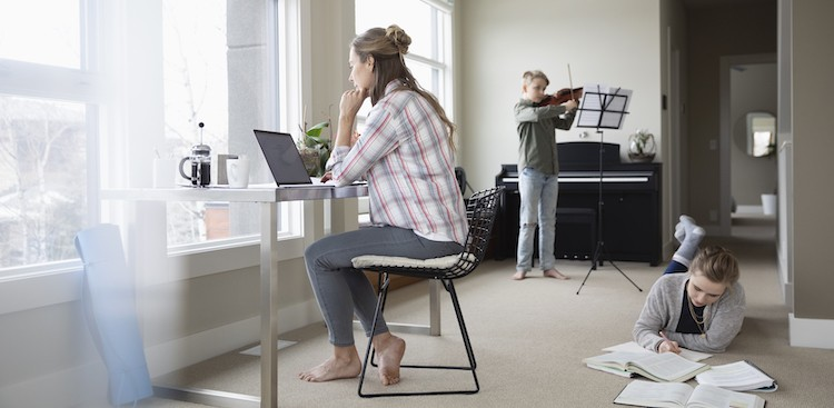 parent at computer with two kids in background