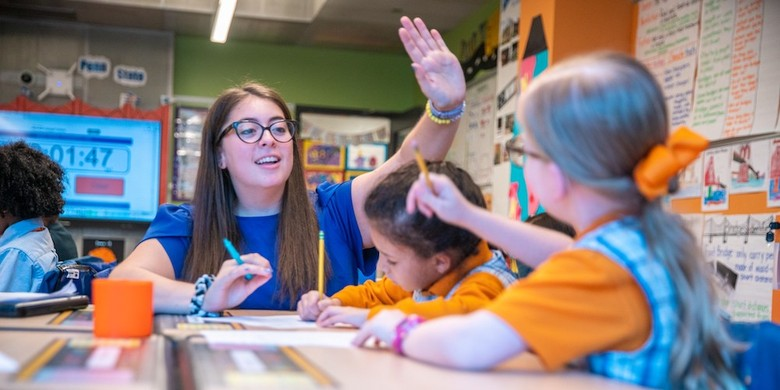 photo of Morgan Hamerman high-fiving a student in the classroom