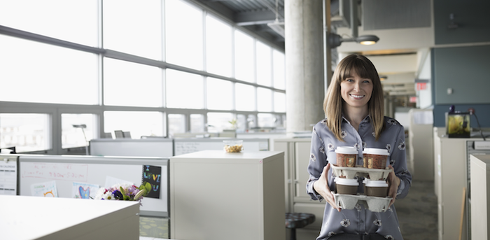 person carrying trays of coffee in an office