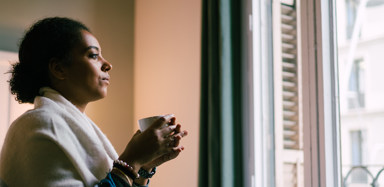 person sitting at home holding a mug and staring out the window