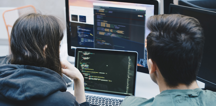 two people looking at code on computer screens