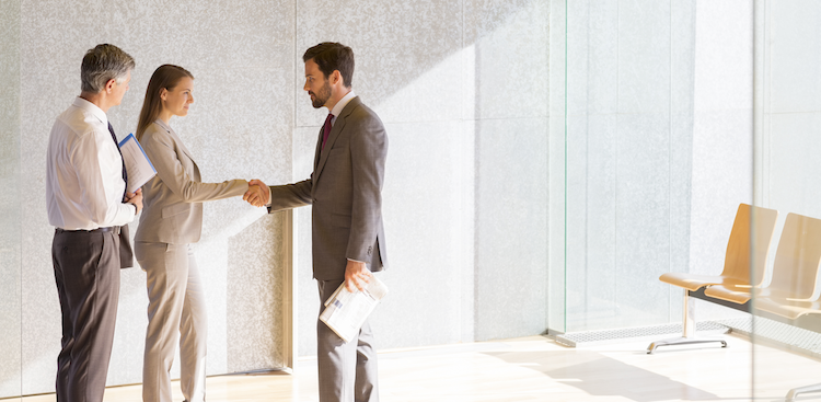 people shaking hands in the lobby of an office
