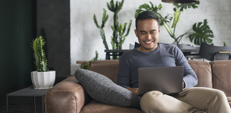 person sitting on a couch with a laptop