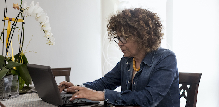 person sitting at a table at home working on a laptop