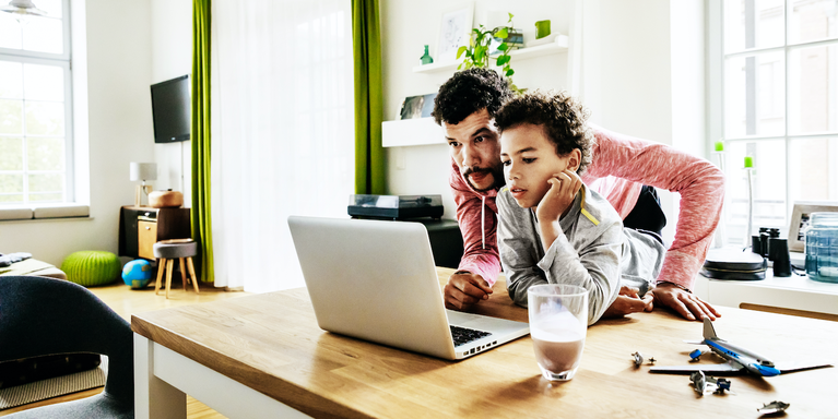 parent and child looking at a laptop screen together at home