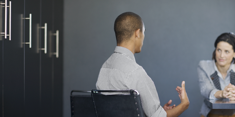 two people sitting in a conference room at a job interview, one of them speaking and gesturing with their hands