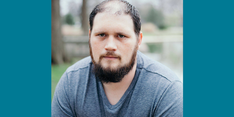 person with beard and gray T-shirt sitting outside