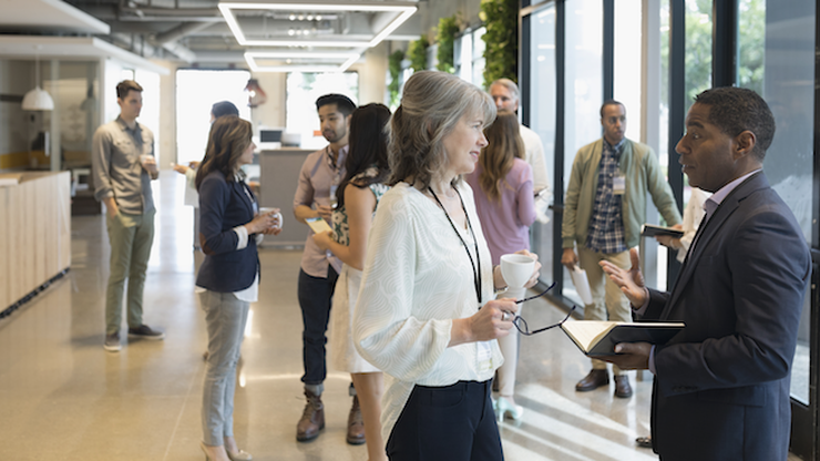 people networking in an office lobby