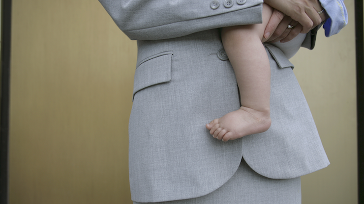 person in a suit holding a baby