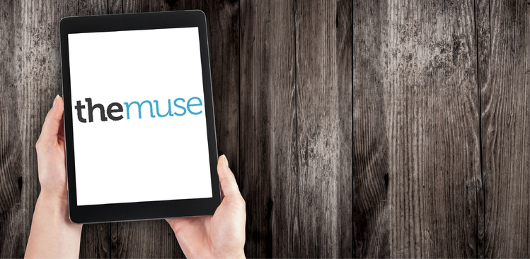 Hands holding iPad with The Muse logo against wood background