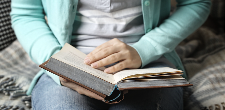 Woman in turquoise cardigan reading book